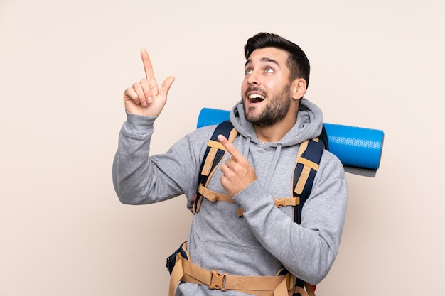 Young mountaineer man with a big backpack pointing with the index finger a great idea