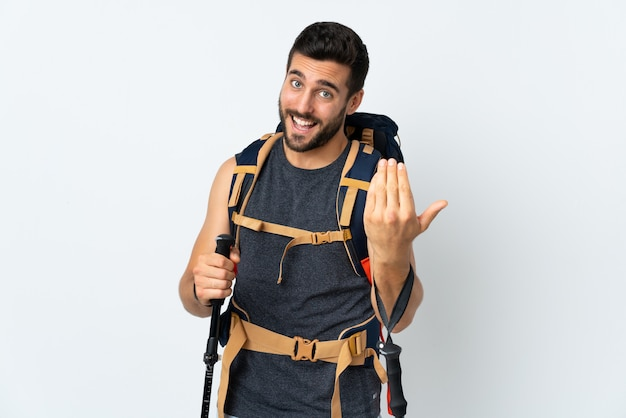 Young mountaineer man with a big backpack and trekking poles isolated on white wall inviting to come