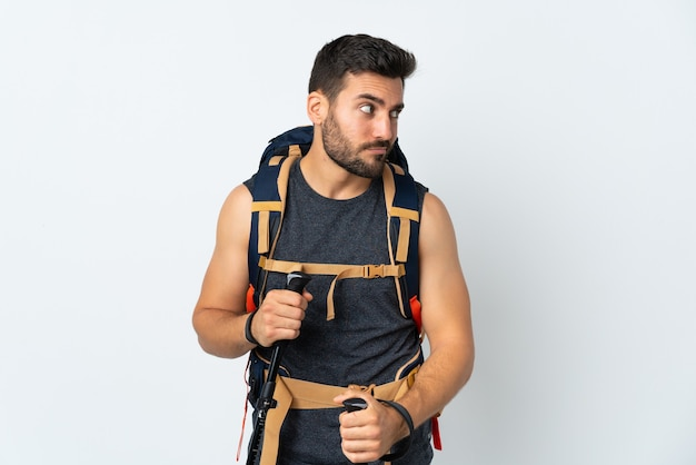 Young mountaineer man with a big backpack and trekking poles isolated on white wall thinking an idea