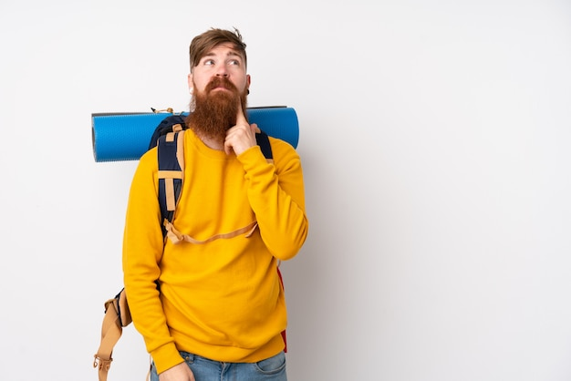 Young mountaineer man with a big backpack over white wall thinking an idea