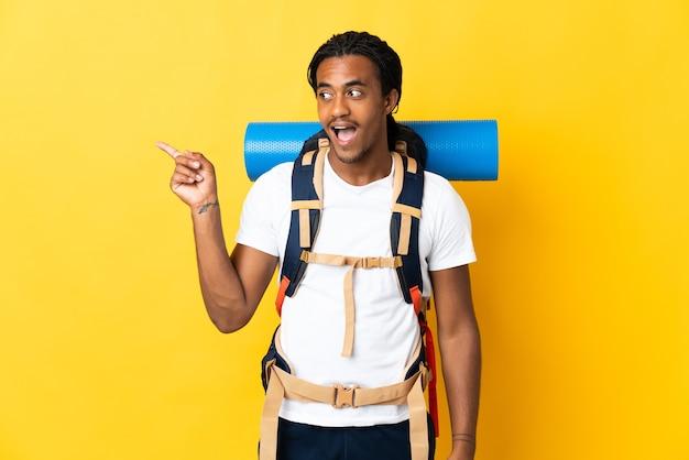 指を持ち上げながら解決策を実現することを意図して黄色の背景に分離された大きなバックパックと三つ編みの若い登山家の男