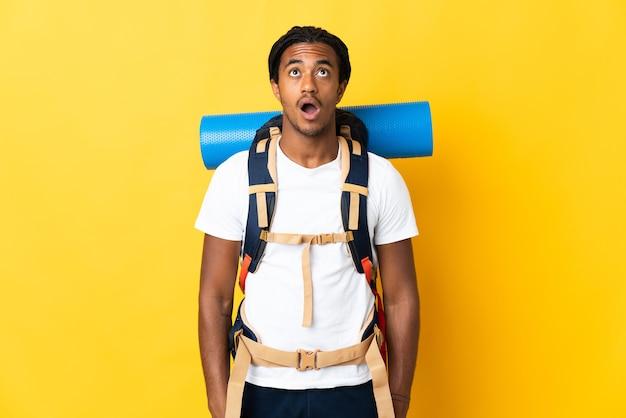 Молодой альпинист с косами с большим рюкзаком на желтом фоне смотрит вверх и с удивленным выражением лица
