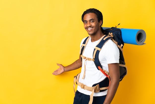 노란색 벽에 고립 된 큰 배낭 머리띠와 젊은 산악인 남자가 와서 초대하기 위해 손을 옆으로 확장
