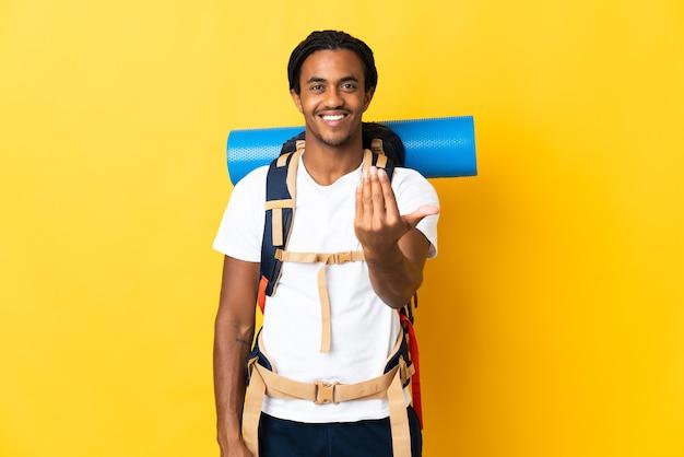 손으로와 서 초대하는 노란색 벽에 고립 된 큰 배낭 머리 띠와 젊은 산악인 남자. 와줘서 행복해