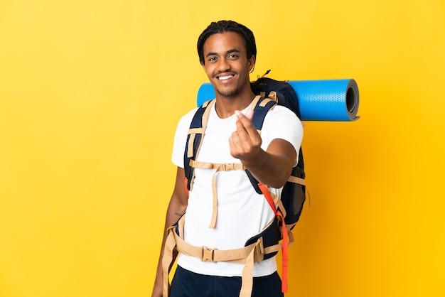 Молодой альпинист с косами с большим рюкзаком изолирован на желтой стене делает денежный жест