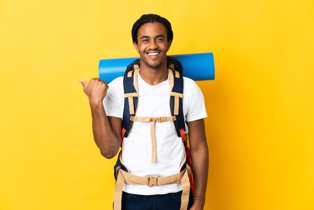 Молодой альпинист с косами с большим рюкзаком изолирован на желтой стене, указывая в сторону, чтобы представить продукт