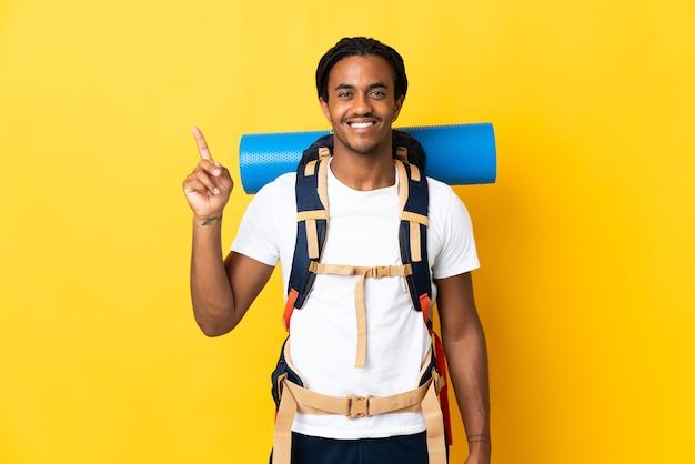 Молодой альпинист с косами с большим рюкзаком изолирован на желтой стене, указывая на отличную идею