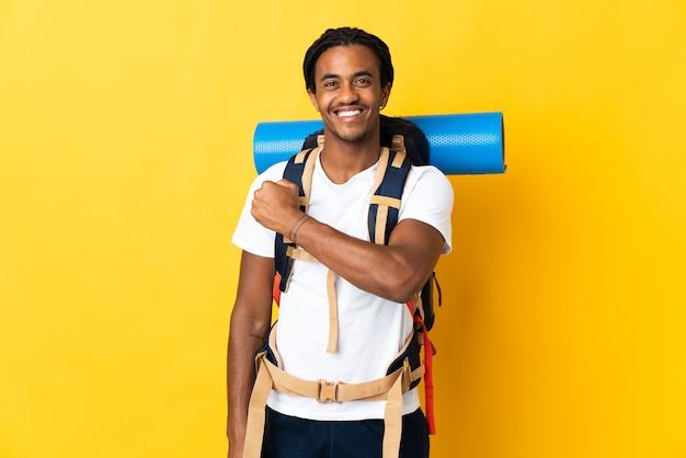 Young mountaineer man with braids with a big backpack isolated on yellow background celebrating a victory