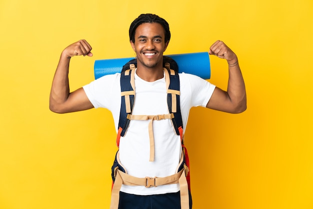 Young mountaineer man with braids with a big backpack isolated on yellow background doing strong gesture