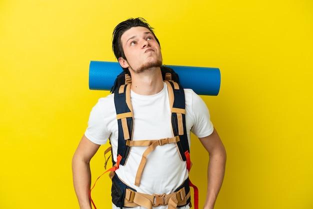 黄色の背景に分離され、見上げる大きなバックパックを持つ若い登山家ロシア人