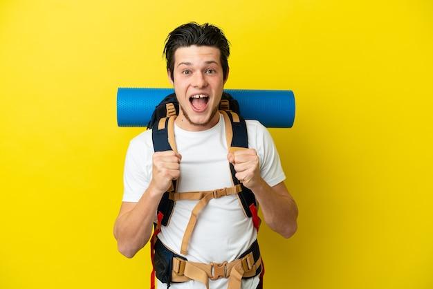 勝者の位置での勝利を祝う黄色の背景に分離された大きなバックパックを持つ若い登山家ロシア人