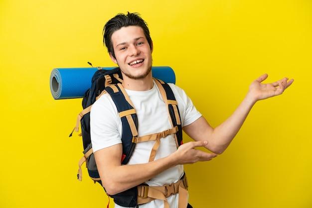 큰 배낭을 메고 노란색 배경에 격리된 젊은 산악인 러시아 남자는 초대하기 위해 손을 옆으로 내밀었다