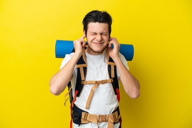 Молодой российский альпинист с большим рюкзаком на желтом фоне разочарован и закрывает уши