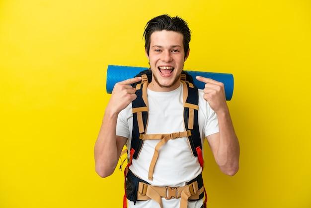 Молодой российский альпинист с большим рюкзаком на желтом фоне показывает палец вверх