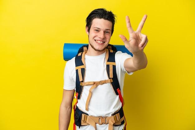 幸せで、指で3を数える黄色の背景に分離された大きなバックパックを持つ若い登山家ロシア人