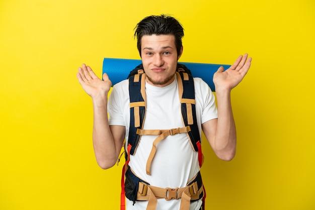 Молодой российский альпинист с большим рюкзаком, изолированным на желтом фоне, сомневается, поднимая руки