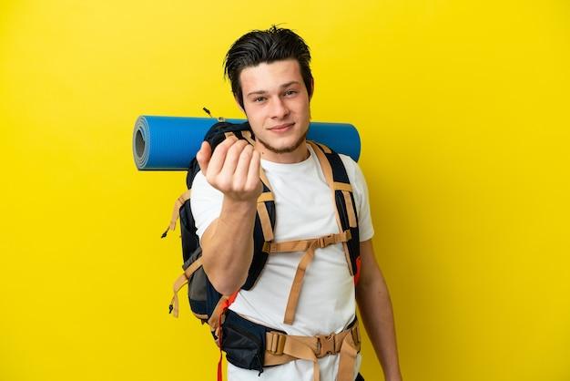 손으로와 서 초대하는 노란색 배경에 고립 된 큰 배낭 젊은 산악인 러시아 남자. 와줘서 행복해