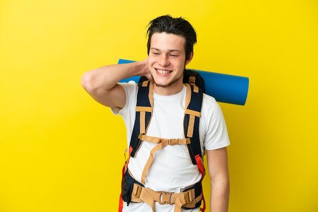 Молодой альпинист русский человек с большим рюкзаком на желтом фоне смеется