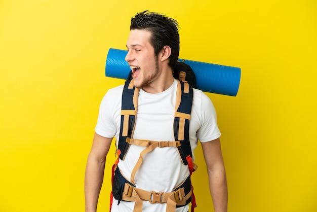 Молодой российский альпинист с большим рюкзаком на желтом фоне смотрит в сторону