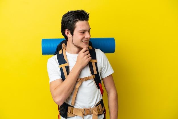 Молодой российский альпинист с большим рюкзаком, изолированным на желтом фоне, смотрит в сторону и улыбается