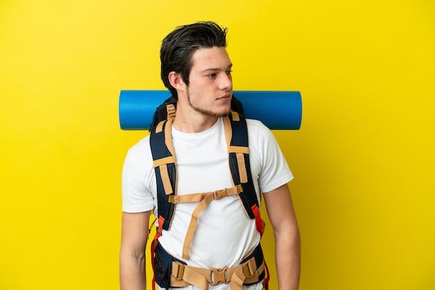 Молодой российский альпинист с большим рюкзаком, изолированным на желтом фоне, глядя в сторону