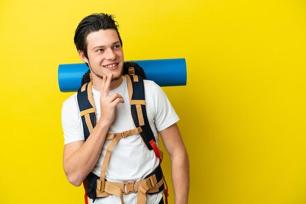 Молодой российский альпинист с большим рюкзаком на желтом фоне смотрит вверх, улыбаясь