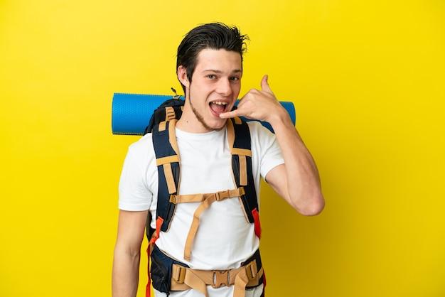 電話ジェスチャーを作る黄色の背景に分離された大きなバックパックを持つ若い登山家ロシア人。コールバックサイン
