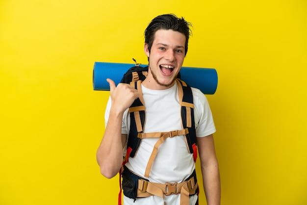 Молодой российский альпинист с большим рюкзаком, изолированным на желтом фоне, указывая в сторону, чтобы представить продукт