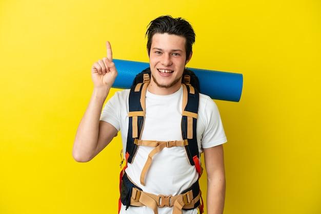 素晴らしいアイデアを指している黄色の背景に分離された大きなバックパックを持つ若い登山家ロシア人