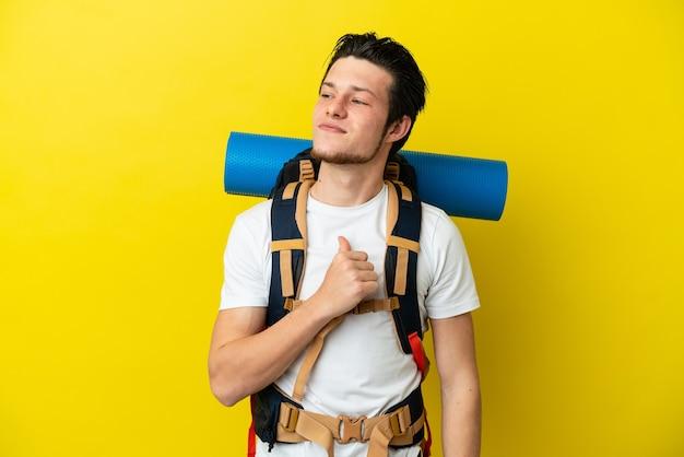 Молодой русский альпинист с большим рюкзаком, изолированным на желтом фоне, гордый и самодовольный