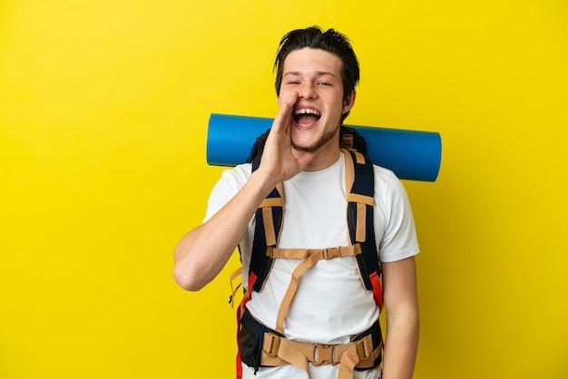 Молодой российский альпинист с большим рюкзаком, изолированным на желтом фоне, кричит с широко открытым ртом