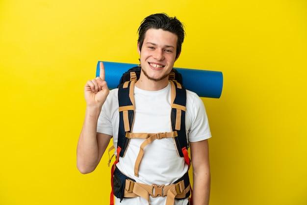 Молодой российский альпинист с большим рюкзаком на желтом фоне показывает и поднимает палец в знак лучших
