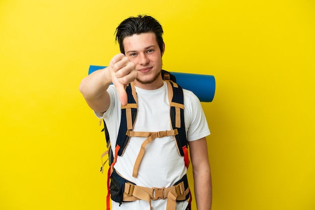 노란색 배경에 격리된 큰 배낭을 메고 부정적인 표정으로 엄지손가락을 아래로 내리는 젊은 산악인 러시아 남자