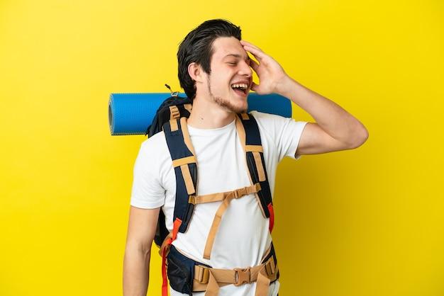 Молодой российский альпинист с большим рюкзаком на желтом фоне много улыбается