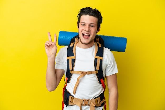 笑顔と勝利の兆候を示す黄色の背景に分離された大きなバックパックを持つ若い登山家ロシア人