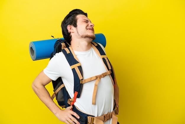 Молодой российский альпинист с большим рюкзаком на желтом фоне страдает от боли в спине из-за того, что приложил усилие