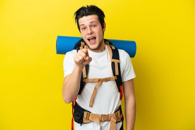 黄色の背景に分離された大きなバックパックを持つ若い登山家ロシア人は驚いて正面を指しています