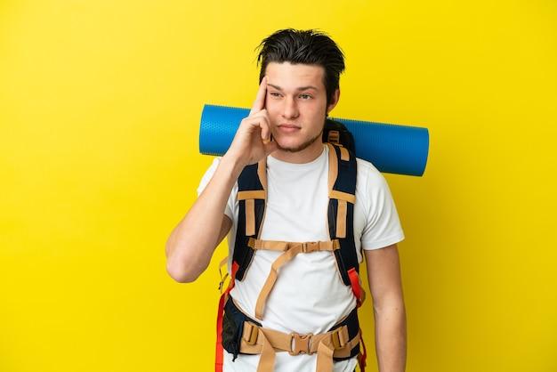 Молодой российский альпинист с большим рюкзаком на желтом фоне думает об идее