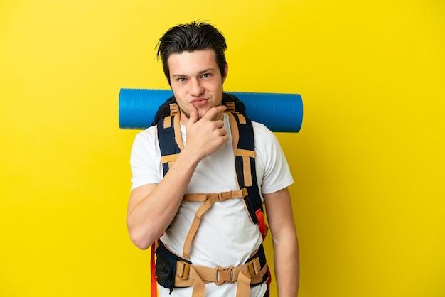黄色の背景思考に分離された大きなバックパックを持つ若い登山家ロシア人