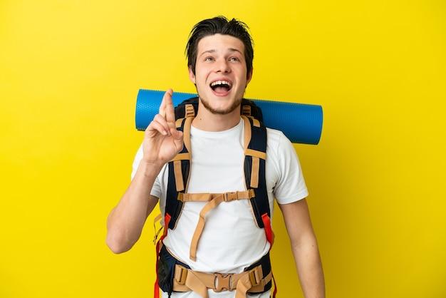 Молодой российский альпинист с большим рюкзаком, изолированным на желтом фоне со скрещенными пальцами и желающим всего наилучшего