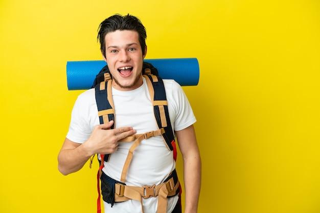 Молодой российский альпинист с большим рюкзаком изолирован на желтом фоне с удивленным выражением лица