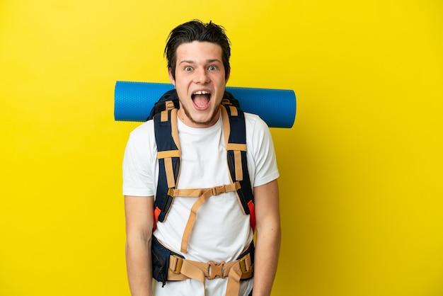 驚きの表情で黄色の背景に分離された大きなバックパックを持つ若い登山家ロシア人