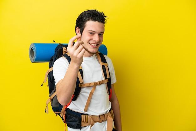 Молодой россиянин альпинист с большим рюкзаком изолирован на желтой стене делает денежный жест