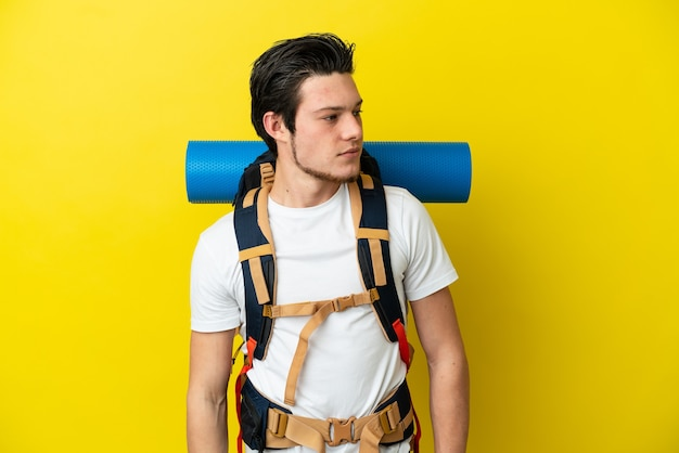 Young mountaineer russian man with a big backpack isolated on yellow background looking to the side