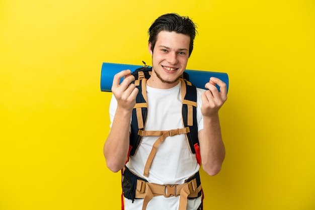 Young mountaineer russian man with a big backpack isolated on yellow background making money gesture