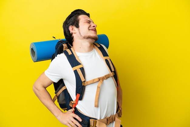 Young mountaineer russian man with a big backpack isolated on yellow background suffering from backache for having made an effort