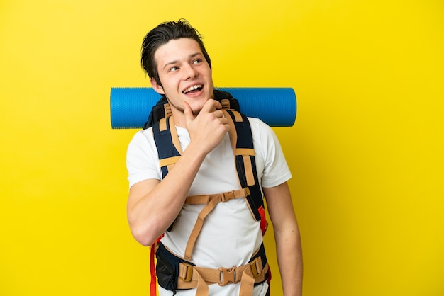 Young mountaineer russian man with a big backpack isolated on yellow background thinking an idea while looking up