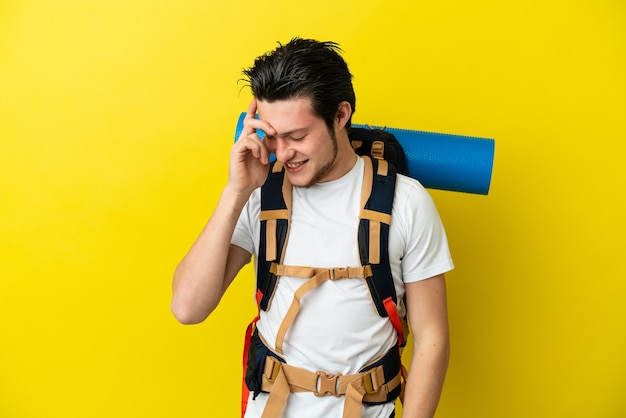 Young mountaineer russian man with a big backpack isolated on yellow wall laughing