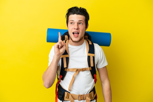 Young mountaineer russian man with a big backpack isolated on yellow wall thinking an idea pointing the finger up