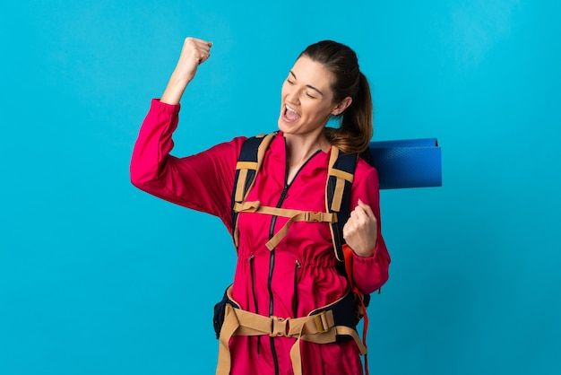 Young mountaineer woman over isolated blue wall celebrating a victory
